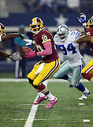 Washington Redskins quarterback Robert Griffin III (10) looks to hand off the ball while pressured by Dallas Cowboys defensive end DeMarcus Ware (94) during the NFL week 6 football game against the Dallas Cowboys on Sunday, Oct. 13, 2013 in Arlington, Texas. The Cowboys won the game 31-16. ©Paul Anthony Spinelli