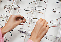 Woman pulling glasses from display rack close up of hands