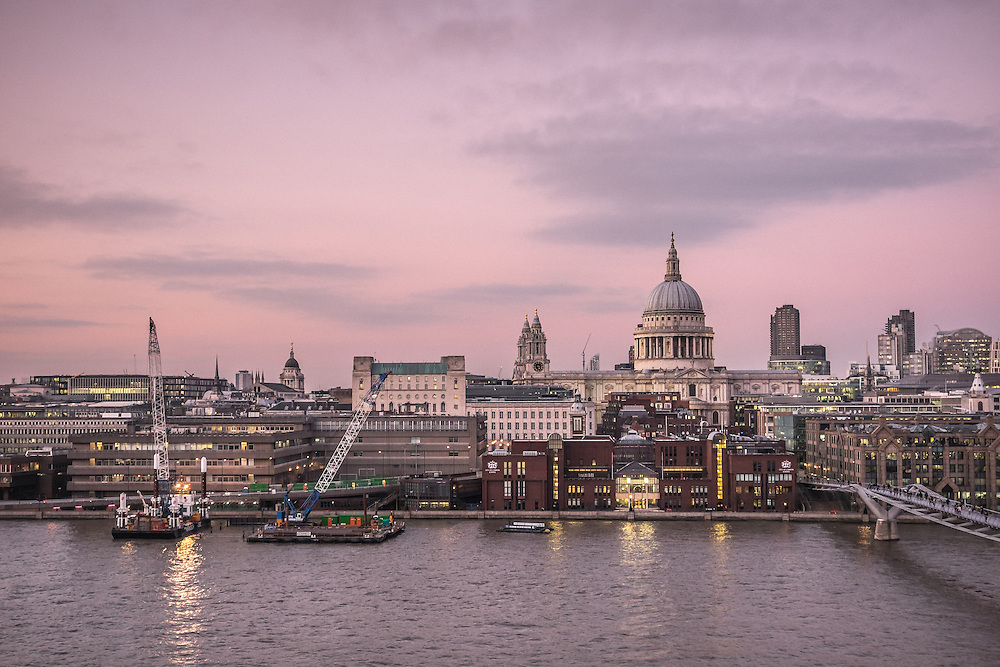St Paul's Cathedral, the Millennium Bridge, and the river Thames in London, glowing under the pink dusk of a summer's sky