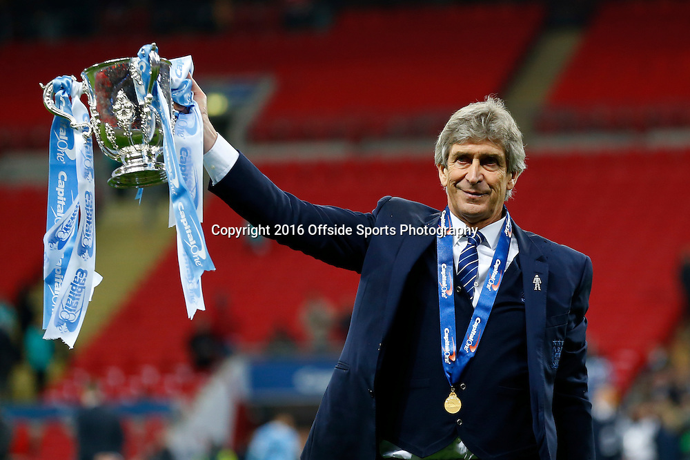 28 February 2016 - The Capital One Cup Final - Liverpool v Manchester City - Manuel Pellegrini, Manager of Manchester City poses with the trophy - Photo: Marc Atkins / Offside.