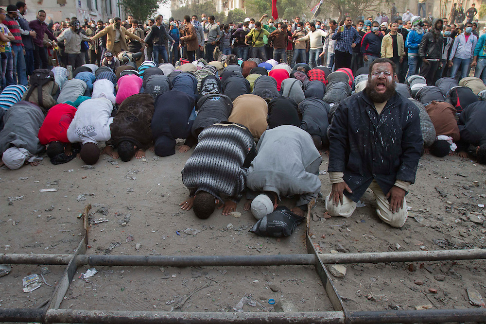 Egyptian demostrators pause during clahses to pray next to Tahrir Square on November 22, 2011 photo by: Maya Levin