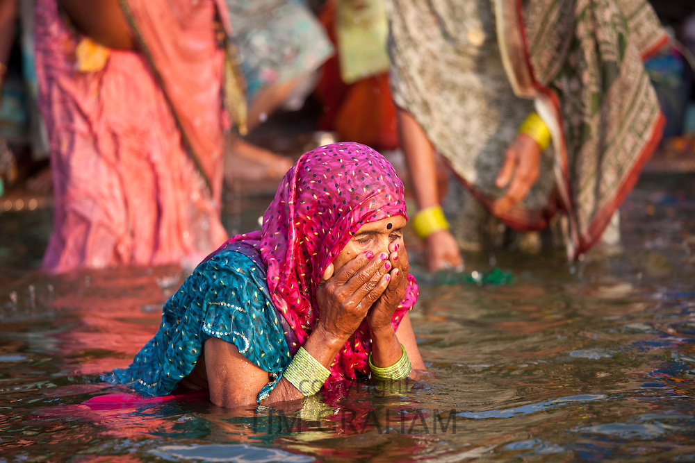 Indian Hindu pilgrim woman bathing in The Ganges River at Dashashwamedh Ghat in Holy City of Varanasi, Benares, India