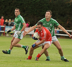 Ballintubber's Alan Plunkett tries to evade the tackle during the senior chanpionship match on saturday evening last.<br /> Pic Conor McKeown
