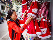 """22 DECEMBER 2017 - HANOI, VIETNAM: A woman sets out the Santa Claus hats she sells on the streets of Hanoi. Christmas is widely celebrated as a commercial event in Vietnam. The old quarter is the heart of Hanoi, with narrow streets and lots of small shops but it's being """"gentrified"""" because of tourism and some of the shops are being turned into hotels and cafes for tourists and wealthy Vietnamese.    PHOTO BY JACK KURTZ"""