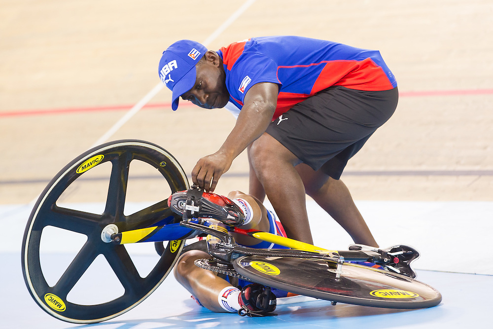 A coach attends to Lisandra Guerra of Cuba after she crashed during the women's cycling sprint quarterfinals at the 2015 Pan American Games in Toronto, Canada, July 18,  2015.  AFP PHOTO/GEOFF ROBINS