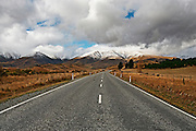 road to the mountains, snow capped and shrouded in mountain cloud, central otago, new zealand