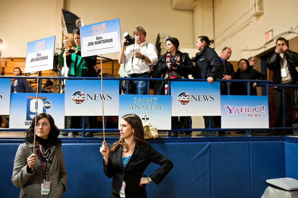 Debate staff hold signs for Republican presidential candidate Jon Huntsman in the spin room following the WMUR/ABC News Debate at Saint Anselm College on Saturday, January 7, 2012 in Manchester, NH. Brendan Hoffman for the New York Times