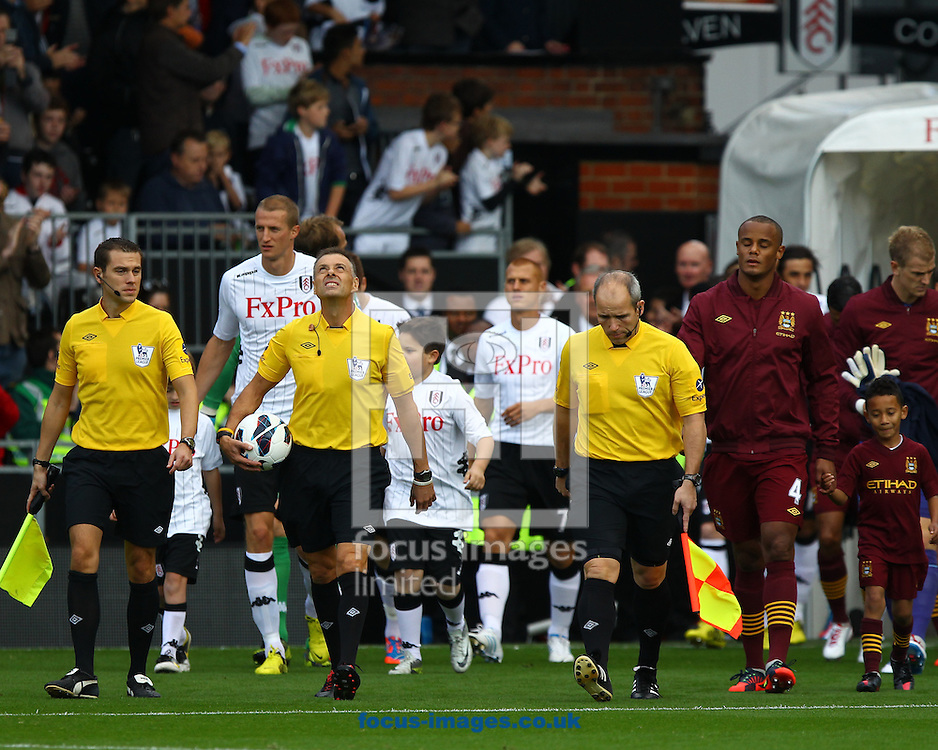 Picture by John  Rainford/Focus Images Ltd +44 7506 538356.29/09/2012.Referee Mark Halsey leads out Fulham and Manchester City for the Barclays Premier League match at Craven Cottage, London.