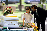 An uncle comforts his nephew at the funeral of his foster brother. The three year old was killed when he was returned to his biological parents
