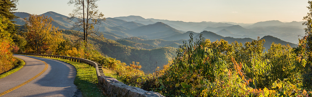 See a lovely sunset view of the Blue Ridge Mountains (a subset of the Appalachian Mountains) at Chimney Rock Mountain Overlook (Milepost 44.9, elevation 2485 feet) on the Blue Ridge Parkway, near Buena Vista, Virginia, USA. Local trees release hydrocarbons into the atmosphere and create a characteristic blue haze on pristine days as seen in this photo; but more often a white or gray haze obscures distant views due to air pollution. The scenic 469-mile Blue Ridge Parkway connects Shenandoah National Park (in Virginia) with Great Smoky Mountains National Park in North Carolina, following crestlines and the Appalachian Trail. This panorama was stitched from 4 overlapping photos.
