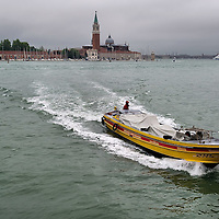 VENICE, ITALY - JUNE 07:   A freight boat crosses St Mark's Basin under a heavy thunderstom on June 7, 2011 in Venice, Italy. Thunderstorms and heavy rain have hit Venice causing an out season high tide of 90 cm flooding St Mark's square.