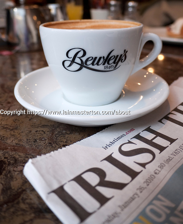 Detail of coffee cup and Irish Times newspaper in famous Bewley's cafe on Grafton Street in Dublin Ireland