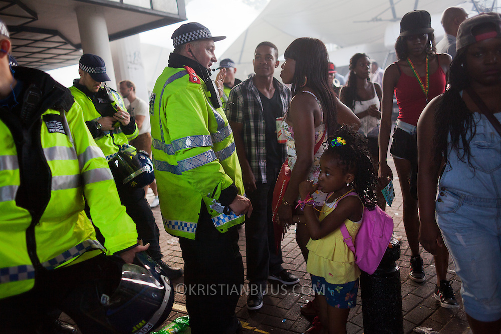 A young black woman with a small girl talks to a police officer next to Portobello Road marketThe Notting Hill Carnival has been running since 1966 and is every year attended by up to a million people. The carnival is a mix of amazing dance parades and street parties with a distinct Caribbean feel.