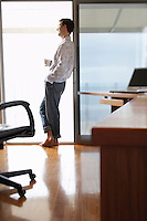Man standing in home office leaning on sliding door side view.