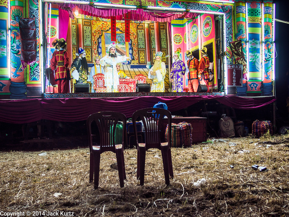 "28 JANUARY 2014 - BANGKOK, THAILAND: The Tear Kia Ee Lye Heng opera troupe performs in Bangkok. They were performing for a business in the Min Buri district of Bangkok for the Lunar New Year, which this year is Jan 31. The business hired them to make merit. The performance was free to the community but nobody came. Chinese opera was once very popular in Thailand, where it is called ""Ngiew."" It is usually performed in the Teochew language. Millions of Teochew speaking Chinese emigrated to Thailand (then Siam) in the 18th and 19th centuries and brought their cultural practices with them. Recently the popularity of ngiew has faded as people turn to performances of opera on DVD or movies. There are still as many 30 Chinese opera troupes left in Bangkok and its environs. They are especially busy during Chinese New Year when they travel from Chinese temple to Chinese temple performing on stages they put up in streets near the temple, sometimes sleeping on hammocks they sling under their stage. They are also frequently hired by Chinese owned businesses to perform as a form of merit making.    PHOTO BY JACK KURTZ"