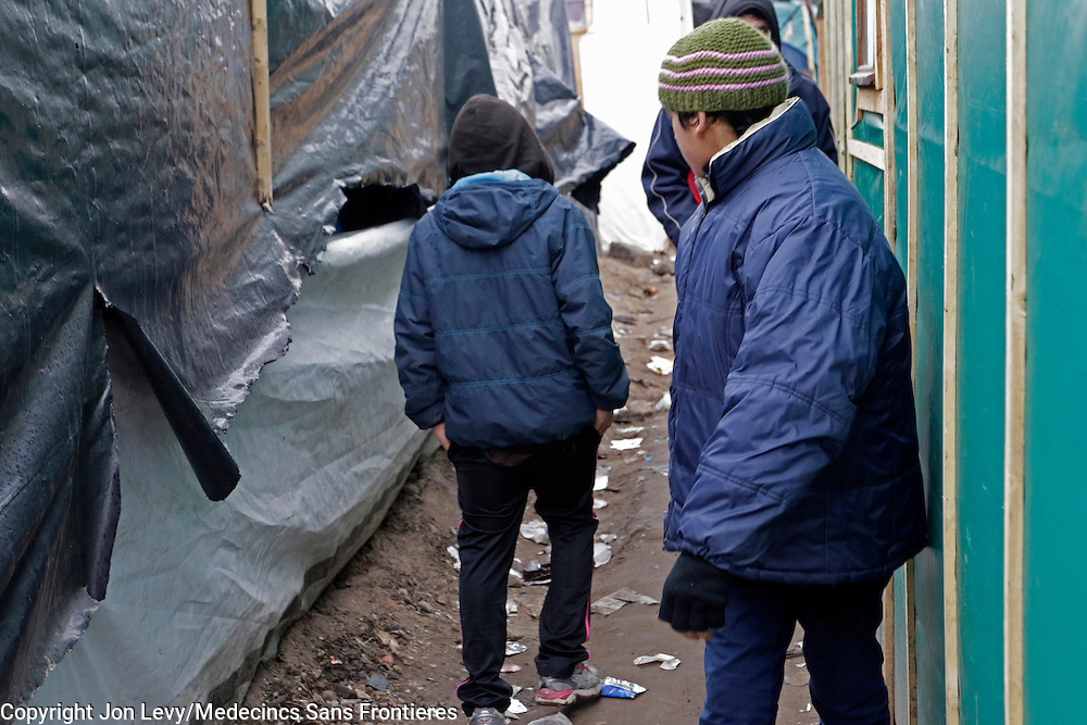 An 11-year-old unaccomapnied minor (L) from Afghanistan walks  back to his tent in the refugee camp in Calais. He claimed his father is in England and his mother had remained in Afghanistan.<br />