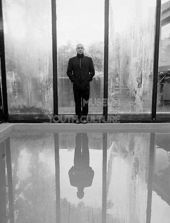 Brian Eno standing on edge of indoor pool.