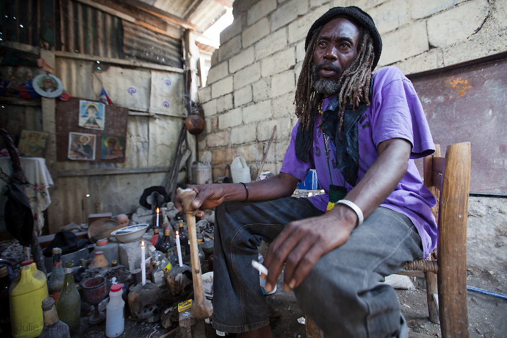 Mondesir Sergo, a voodoo priest in Port-au-Prince sits next to his shrine.Mondesir Sergo has more customers since the earthquake who want to speak to the dead. Voodoo is part of Haitian culture.
