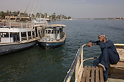 A local man talks on his mobile phone on the top deck of the state-run ferry across the River Nile at Luxor, Nile Valley, Egypt.