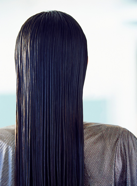 The back of a womans head in a beauty salon showing her wet and combed hair.