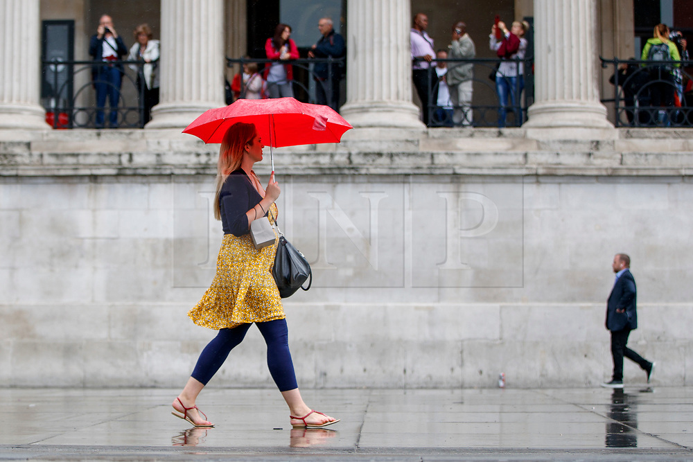 © Licensed to London News Pictures. 27/06/2017. London, UK. People take shelter from the rain in Trafalgar Square, London on Tuesday, 27 June 2017. Photo credit: Tolga Akmen/LNP