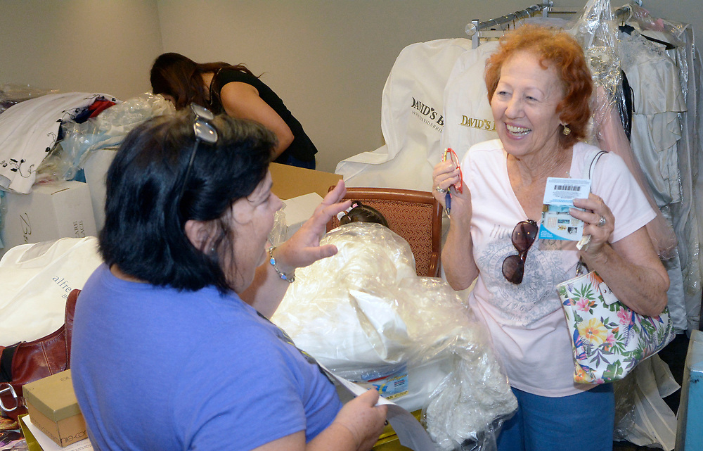 gbs072717a/ASEC -- Stacy Blackwell with New Mexico Wedding Expo, left, takes a wedding dress donated by Julie Weaver of Albuquerque, for women left out in the cold by the closing of Alfred Angelo bridal shop on Thursday, July 27, 2017. (Greg Sorber/Albuquerque Journal)