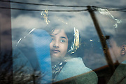 A refugee child looks through the window of a police van shortly after arriving by dinghy on the Greek island of Lesvos from Turkey. The number of refugee arrivals by sea to Greece so far this year is more than 6,000, with approximately 54,000 arrivals in Italy, according to UNHCR data.