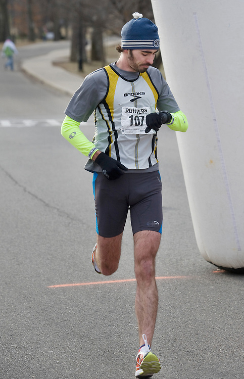 Dave Bresnahan, the winner of the 2009 5K Frostbite Run checks his time as he crosses the finish line in 16:30.  Approximately 100 people braved the cold weather to participate in this year's run.