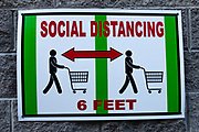Brooklyn, NY - 7 April 2020. At 8 AM, the line to enter the grocery and warehouse store Costco on 3rd Avenue already stretches across the front of the building and along the length of the side back to 2d Avenue. This sign is one of several posted on the sides of the store.