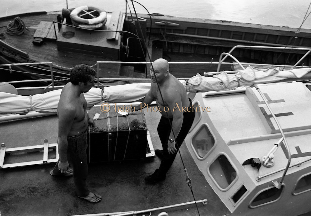 """03/08/1967<br /> 08/03/1967<br /> 03 August 1967<br /> Arrival of """"Saint Brendan II"""" in Dublin. Image shows Captain Louis Lourmais (rright) and Vint Lloyd of Nova Scotia, checking equipment and supplies for the """"Saint Brendan II"""" a curragh they hoped to sail from Fenit Co. Kerry to America by the Northern Route (Ireland, Iceland, Greenland, North America) and land between Boston and Rhode Island to see if Brendan the Navigator could have reached North America in the 6th century AD. Captain Lourmais had the curragh built to specifications resembling those of what was believed to be the type of craft available in the  6th century. It was the first time the curragh had been in the water since its construction."""