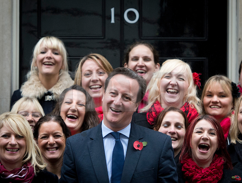 © London News Pictures. 10/11/2012. London, UK. British Prime Minister David Cameron poses in front of 10 Downing Street with members of the Military Wives Choir who performed on Downing Street before members of the Royal Marines from Commando 999 (Royal Marines who serve with the UK emergency services) took part in a  speed march for charity around London to raise funds for wounded service personnel. The event takes place on Remembrance weekend.  Photo credit: Ben Cawthra/LNP