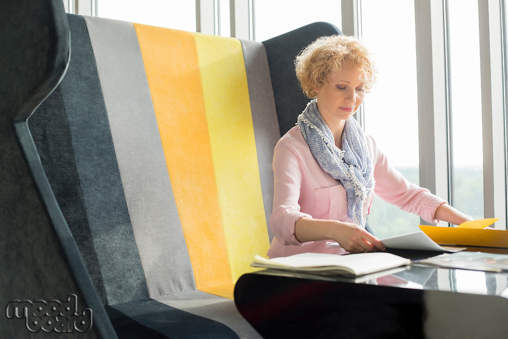 Mid adult businesswoman reading documents at desk in office