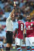 Aston Villa midfielder Idrissa Gana (8) is shown the yellow card by Referee Martin Atkinson during the Barclays Premier League match between Aston Villa and Bournemouth at Villa Park, Birmingham, England on 9 April 2016. Photo by Jon Hobley.