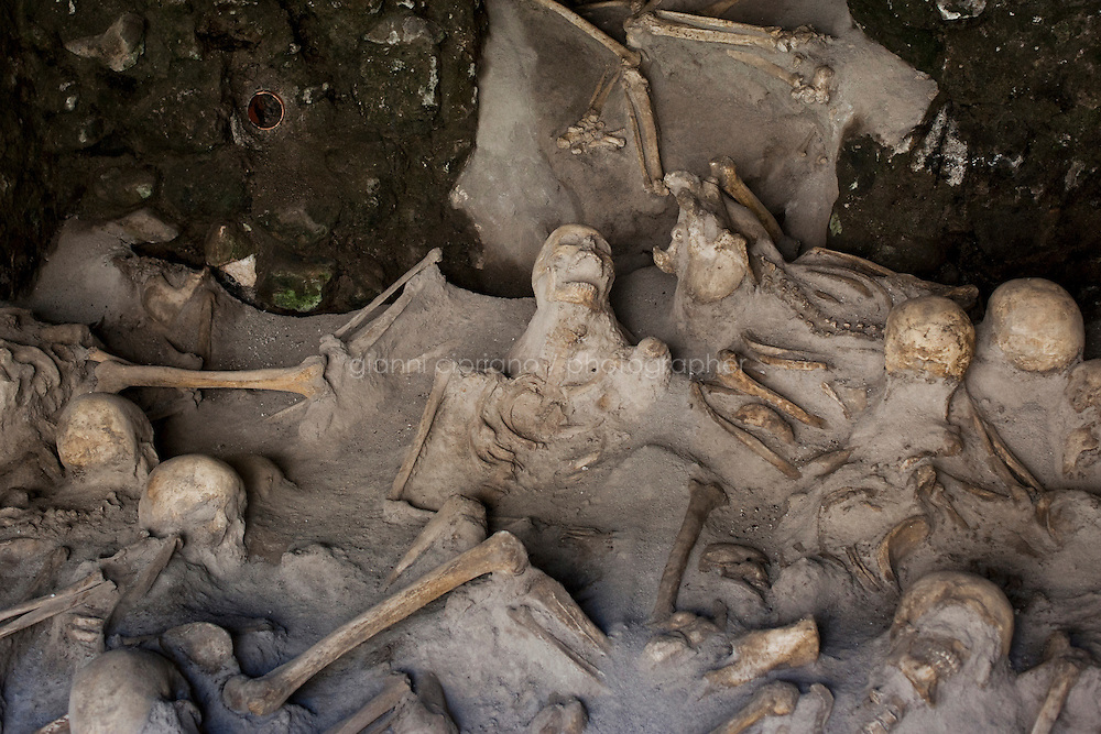 Herculaneum, Italy - 2 August, 2012:  Skeletons are here in one of the six boat chamber of the ancient seafront of Herculaneum, Italy, on 2 August, 2012. Excavations in the port area of Herculaneum initially turned up more than 55 skeletons. The skeletons were found on the seafront, where it is believed they had fled in an attempt to escape the volcanic eruption. About 300 skeletons were founds in the ancient town of Herculaneum.<br /> <br /> The Herculaneum Conservation Project (HCP) is a public/private initiative launched in 2001 for the conservation and enhancement of the archaeological site of Herculaneum. This ancient Roman city in Italy was destroyed and buried along with Pompeii by the volcanic eruption of Mount Vesuvius in AD 79. It has a history of excavation dating back to the early eighteenth century.<br /> The project was set up by David W. Packard of the Packard Humanities Institute, together with Pietro Giovanni Guzzo of the Soprintendenza Archeologica di Pompei, to take the measures necessary to provide a response to the serious condition of the site after decades of neglect.