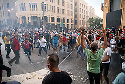 © Licensed to London News Pictures. 10/08/2020. Beirut, Lebanon. Demonstrators pull down a concrete defence wall during clashes with the police and army as they protest against the government following a huge explosion in Beirut port on 4 August. Photo credit : Tom Nicholson/LNP