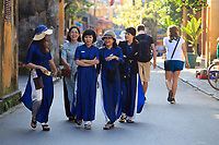 Vietnamese women in the traditional Ao Dai clothing walk the streets of the old town of Hoi An