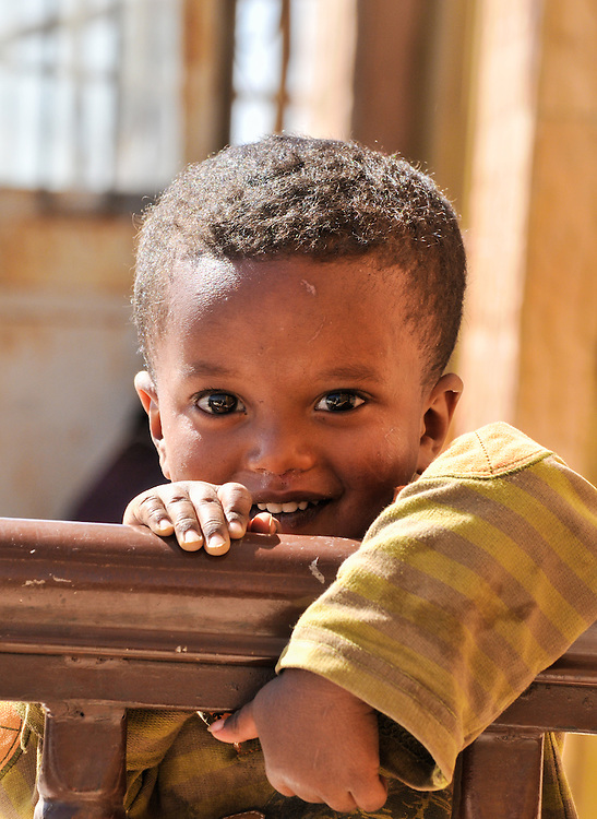 Young boy smiling while leaning over a fence, Debark, Ethiopia.
