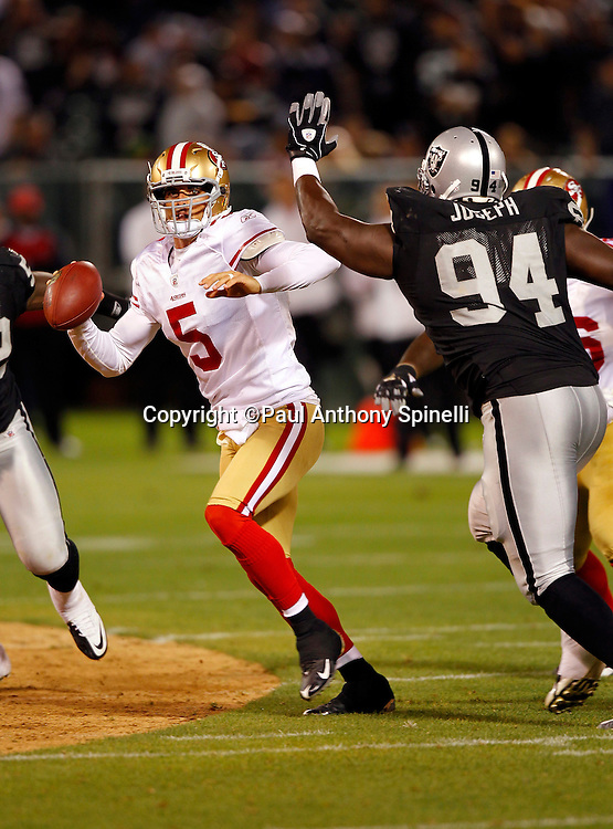 San Francisco 49ers quarterback David Carr (5) gets chased out of the pocket by Oakland Raiders defensive tackle William Joseph (94) during the NFL preseason week 3 football game against the Oakland Raiders on Saturday, August 28, 2010 in Oakland, California. The 49ers won the game 28-24. (©Paul Anthony Spinelli)