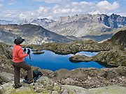 A hiker views Lac Cornu in the Reserve Naturelle Aiguilles Rouges, on the Chamonix-Zermatt Haute Route (High Route) near Chamonix, France, Europe.