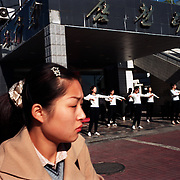 Dandong city, China, 11-2003..North Korean restaurant staff performs routine morning exercises. The waitresses, selected from government officials in North Korea, have been politically trained to operate in a foreign country. ..The restaurant is owned by the North Korean government and the waitresses are under strict control. They are not allowed to walk out of the restaurant unaccompanied. If they escape their family in North Korea would be in trouble...The woman in the foreground is Chinese. ..Ruled by the messianic leader Kim Il Sung and his son Kim Jong Il since 1948, North Korea has stubbornly stuck to its juche (self-reliance) ideology and siege mentality, imposing one Stalinist economic plan after another. Floods, droughts and mismanagement in the 1990s plunged the country into a preventable famine, killing up to three million, or 13 percent of the population. It now depends heavily on Chinese aid...China help North Korea fight the Korean War in the 1950s and continue to have a defence treaty with the Stalinist country..