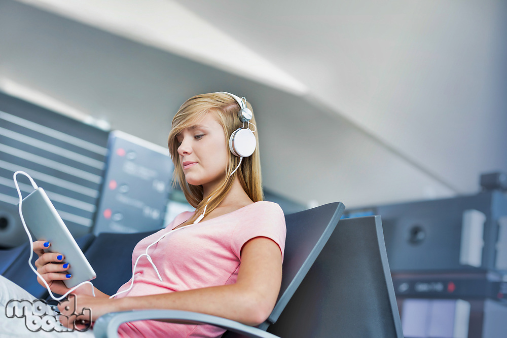 Portrait of young teenage girl sitting while watching movie on her digital tablet with headphones on in airport