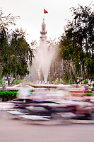 Motorbike blur whizzes by  a fountain that sits in front of a government Municipal Building in Saigon.