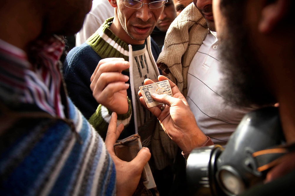 Protesters examine a police ID taken from an undercover Secret Service agent who had attempted to mix into the anti-government crowd in Tahrir Square in Cairo, Egypt on Thursday, Feb. 3, 2011.