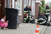 Een meisje en brandweermannen wachten in een zijstraat van het Aakplein de Utrechtse Schepenbuurt op wat komen gaat. Aan het Aakplein in Utrecht is een auto gevonden met mogelijk exposieven. De Explosieven Opruimingsdienst EOD onderzoekt de auto. Het bleek vals alarm.<br /> <br /> A girl is waiting with the fire brigade in front of her house. A car at the Aakplein in Utrecht probably has an explosion on board. The military unit is examining the car. It turned out to be false alarm.