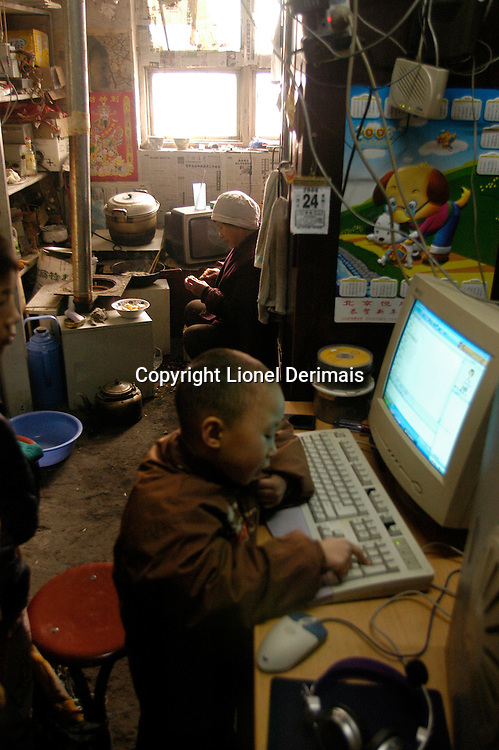 The son of a computer repairman plays while the grandmother peels vegetables. January 2006.                               .