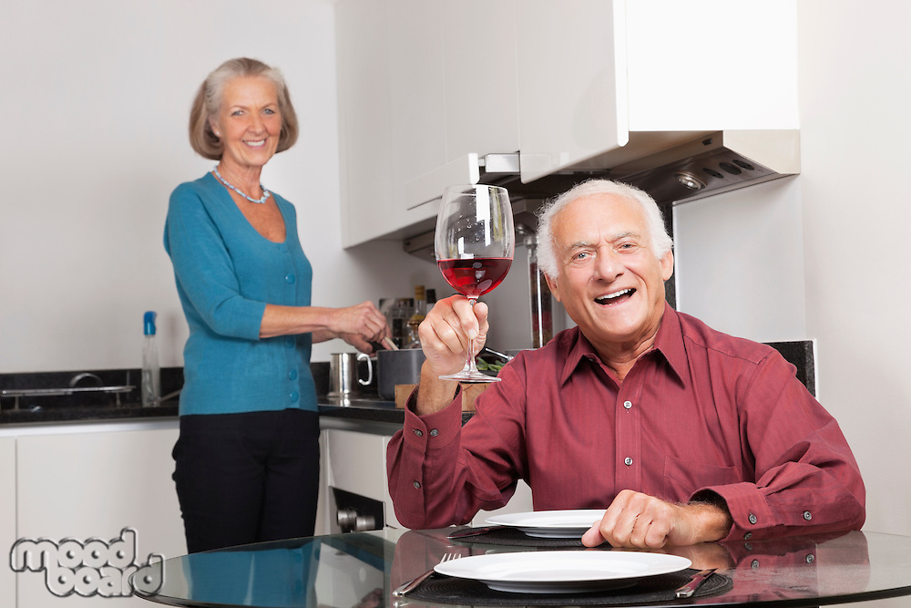 Portrait of happy senior couple at kitchen while man holding up wine glass