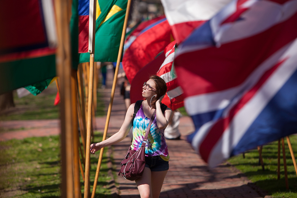 Ohio University student Stephanie Johnson of Marysville, Ohio tours through rows of flags on the college green during the celebration of International Week, that culminated with a street fair Saturday April 19, 2014.  Photo by Ohio University / Jonathan Adams