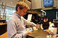 Vitus Ammann, CMO of Monetas, showing how he uses the Monetas app to pay in a Zug Café, Monsieur Baguette, in Zug Kanton, Switzerland/Vitus Ammann, directeur marketing de Monetas, paye avec l'appli Monetas au café Monsieur Baguette, Zoug, Suisse.