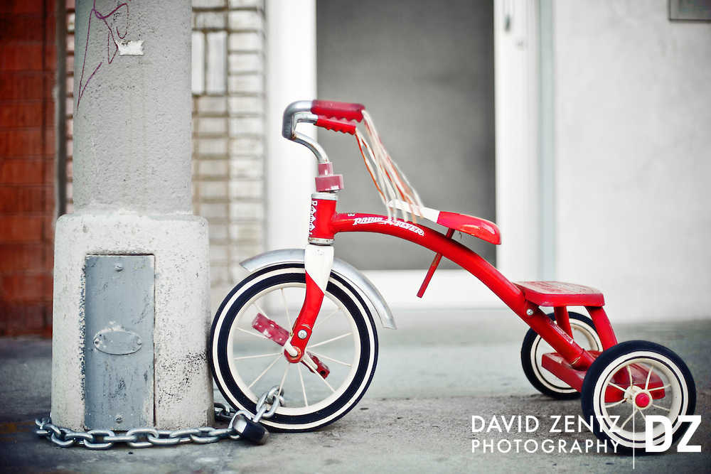A Radio Flyer tricycle chained to a light post on Market Street in Venice, Los Angeles, Calif.