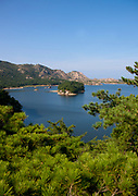 KUMGANG<br /> THE NORTH KOREAN GHOST TOWN<br /> <br /> The first town USA will find on his way to invade NK will be this ghost town where HUnday lost 1 billion USD..<br /> <br /> The Mount Kumgang tourist complex in North Korea, near the DMZ, was built in 1998 by the South Korean giant company Hyundai. The chaebol paid a fee of $1 billion to the North Korean government for 50 years of exclusivity. The cost of the 500-square kilometer complex was $400 million, including hotels, a spa, a fire station, a tourism office, a golf course, a supermarket, a clinic, tours in the mountain... Kumgang resort attracted nearly 2 millions south korean tourists from1998 to 2008.<br /> In July 2008 a South Korean tourist, Miss Park Wang-ja, was shot dead there and South Korea decided to stop all the tours in North Korea. The North Korean government said the tourist entered the military zone, and ignored the warnings from the north korean soldiers.<br /> So in retaliation, North Korea decided to seize the whole tourist complex. This decision was a real drama. Not for the touristic industry only, but for the separated families from the south and the north: Kumgang was also the place where hundreds of North and South Korean relatives were meeting each other for the first time in decades.<br /> For those reasons, since 2008, Mount Kumgang complex has became a ghost town. Only very few western tourists could visit the area.<br /> <br /> Photo shows:   The scenery is wonderful, with mountains peaks everywhere, and pines forest. A short stop in Samil Lake shows an incredible scenery with unspoiled water. A perfect place to make canoe or to rest on a long chair. But nothing has been done.<br /> ©Eric Lafforgue/Exclusivepix Media